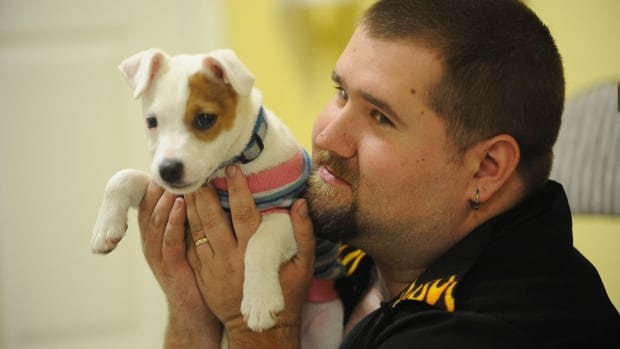 An Iraq War veteran plays with his new puppy to help with his PTSD. The Mental Health Foundation of Nova Scotia is raising money to pay for service dogs for first responders
