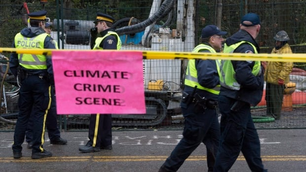 Police patrol as a Kinder Morgan employee drills on Burnaby Mountain in the background as a sign placed by a anti-pipeline demonstrator is pictured in the foreground in Burnaby, B.C., on Monday, Nov. 24, 2014.