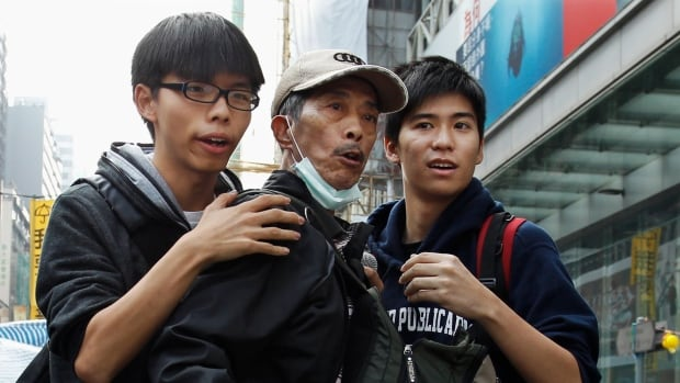 Joshua Wong, left, and Lester Shum, right, both student leaders, hold back a protester behind a barricade while watching police movement at Mong Kok shopping district in Hong Kong on Wednesday.