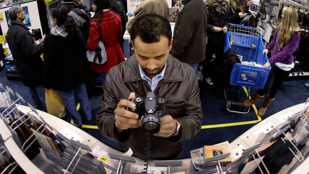 Ripan Bhowmik looks at cameras while shopping at Best Buy in Overland Park, Kan. Americans are expected to spend at the highest rate in three years during what's traditionally the busiest shopping season of the year, according to the National Retail Federation.