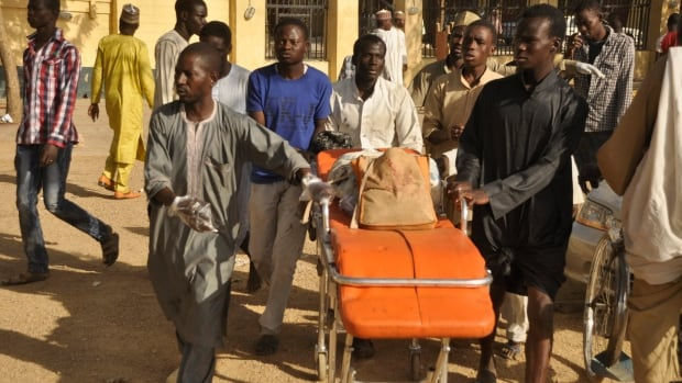 The remains of a victim of the mosque bombing in Kano, Nigeria, are wheeled into a hospital. Gunmen set off three bombs and opened fire on worshippers in an attack that killed scores and bore the hallmarks of Islamist Boko Haram militants.