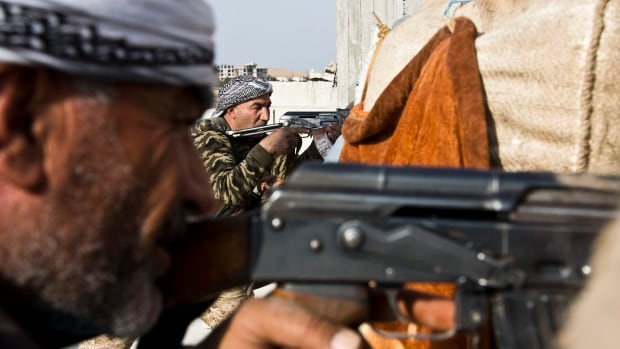 Fighters from the Free Syrian Army and the Kurdish People's Protection Units join forces to fight ISIS in Kobani, Syria. A Kobani-based activist says ISIS fighters have taken positions on the Turkish side of the border and are launching attacks toward the border crossing point.