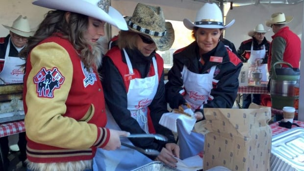 Calgary Stampeders fans hand out free sausages during the Grey Cup pancake breakfast Friday in Vancouver.