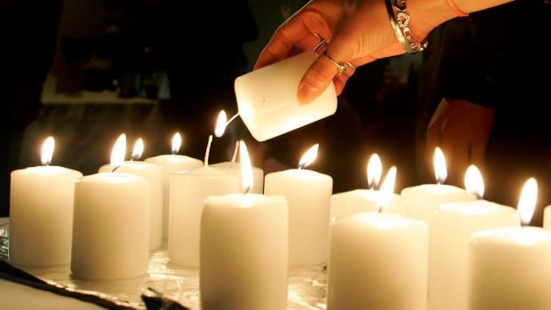 A woman lights candles Wednesday Dec. 6, 2006 in honour of women killed by gun violence during an event in Toronto marking the 17th anniversary of the Ecole Polytechnique massacre in Montreal that left 14 women dead.(CP PHOTO/Adrian Wyld)