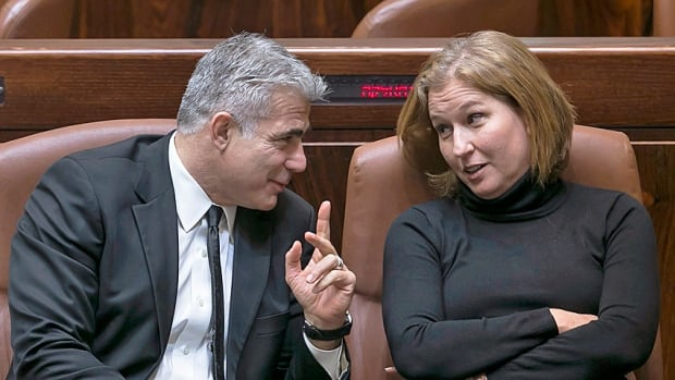 Co-conspirators? Israel's dismissed finance minister Yair Lapid and justice minister Tzipi Livni, leaders of two centrist political parties, talk after a vote to dissolve the Israeli parliament and head to the polls for March 17.