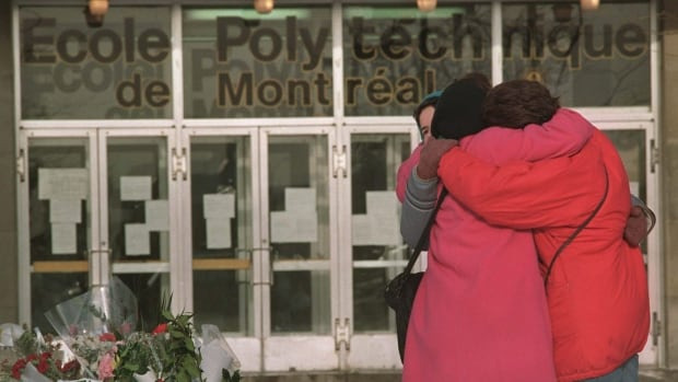 Three  women hug other after laying flowers in front of École Polytechnique​ in Montreal, where a gunman killed 14 women on Dec. 6, 1989.