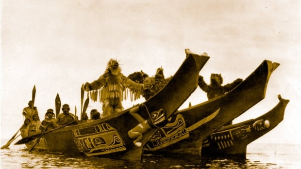 Wasp, Thunderbird and Grizzly Bear dancers perform in the bows of the three canoes as the groom's party approaches the village of the bride's father. Photograph by Edward Schwinke.  IN THE LAND OF THE HEAD HUNTERS (1914).