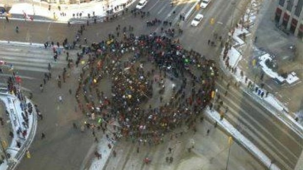Drawn to the sound of the drum, people gather at the round dance at Portage and Main in Winnipeg.