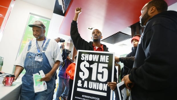 A customer, left, stands at the counter as a group of protesters demonstrates inside the McDonald's restaurant on in Jackson, Miss., on Dec. 4. U.S. wage growth has been lower than in Canada since 2007.