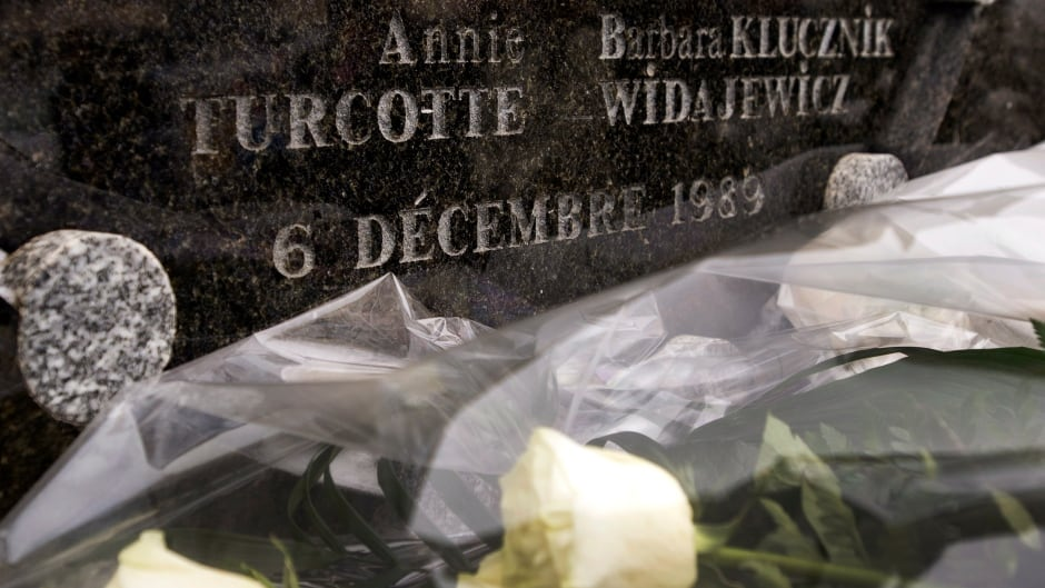 Flowers lay at the base of a memorial plaque to mark the 25th anniversary of the Polytechnique massacre  on Dec. 6, 2014, in Montreal.