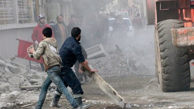 Men clear a damaged site hit by what activists said were airstrikes by forces loyal to Syrian President Bashar al-Assad in eastern Syria last week.  The area is controlled by the Islamic State group, which attacked an air base this week but reportedly has been repelled.