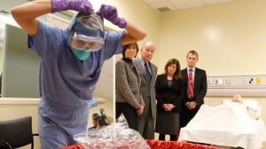 Judith Bosse, (left to right), Assistant Deputy Minister at the Public Health Agency of Canada, Defence Minister Rob Nicholson, Health Minister Rona Ambrose and Dr. Gregory Taylor, Canada's Chief Public Health Officer, watch a nurse demonstrate how to remove protective clothing after treating a hypothetical Ebola patient.