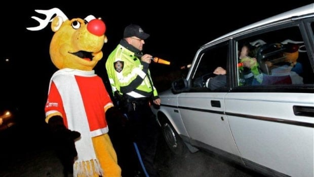 Rudy, Operation Red Nose's reindeer mascot, stands by as a police officer speaks to a volunteer Operation Red Nose driver.