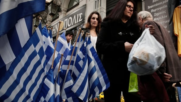 Pedestrians walk past Greek flags for sale in central Athens on Tuesday. The Athens stock market plunged more than 10 per cent as new elections threatened to reopen financial wounds.