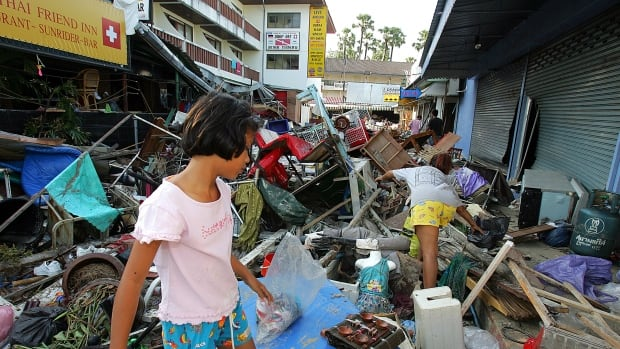 Thai people go through ruins left after devastation caused by tidal waves at Pathong beach, near Phuket, on Dec. 27, 2004.
