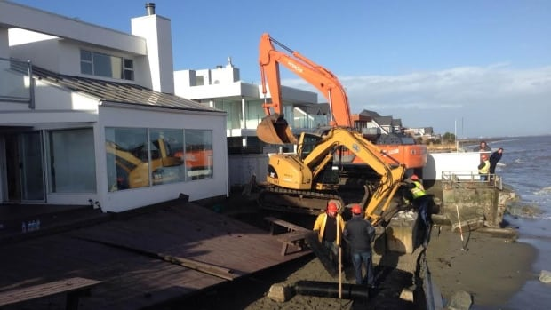 Crews in Tsawwassen, B.C., repair a seawall protecting a home on Tuesday after it was knocked down by a storm surge during a recent high tide.