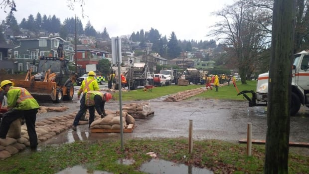 Crews in Vancouver place sandbags along NW Marine Drive to prepare for an expected storm surge earlier this month.