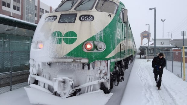A commuter walks past a snow-covered GO-train in Oakville. According to