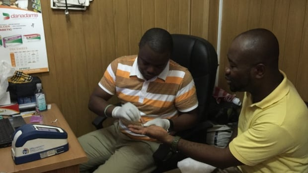 Pharmacist Kwaku Ankamah draws blood for a rapid malaria test from Kwadwo Ankamah at a dispensary in Accra.