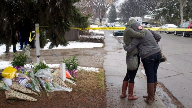 Women cry and hug beside a makeshift memorial near the scene of the multiple fatal stabbings in northwest Calgary last April. The man accused in the crime, Matthew de Grood, is behind bars until his preliminary trial expected in March.
