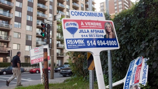 For sale signs stand in front of a condominium in Montreal. Condos in the eastern end of the city led much of the overall real estate market in the fourth quarter of 2015.