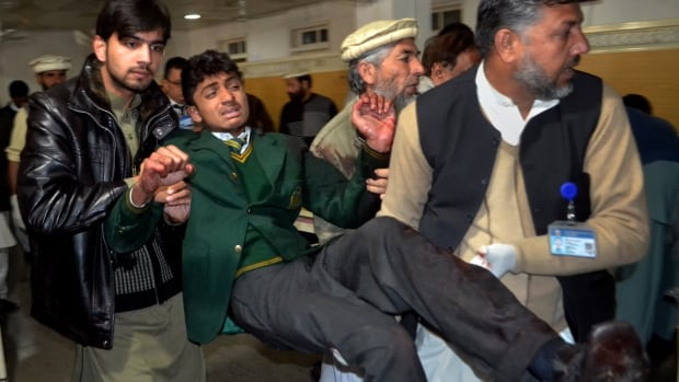 Pakistani volunteers carry a student injured in the shootout at a school under attack by Taliban gunmen earlier this week. The attacked killed a total of 148 people, mostly children.