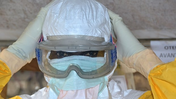 A health worker at the Donka treatment centre for Ebola in Conakry, Guinea. There is no clear upward or downward trend of new cases in the West African nation, the World Health Organization says.