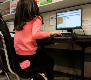 Young girl working on computer coding