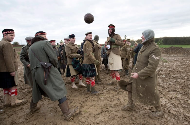 actors dressed in world war i british and german uniforms kick around a soccer ball during a re enactment of the 1914 christmas truce - Wwi Christmas Truce
