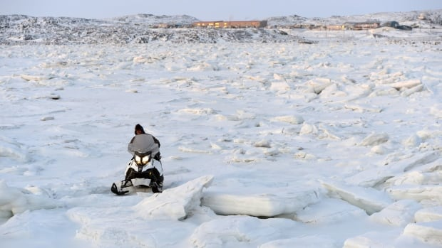 A snowmobiler makes his way through the ice on Frobisher Bay outside of Iqaluit. Canada's Arctic capital of 7,000, like other Arctic communities, is growing rapidly, in part due to migration from smaller communities, according to the second Arctic Human Development Report.