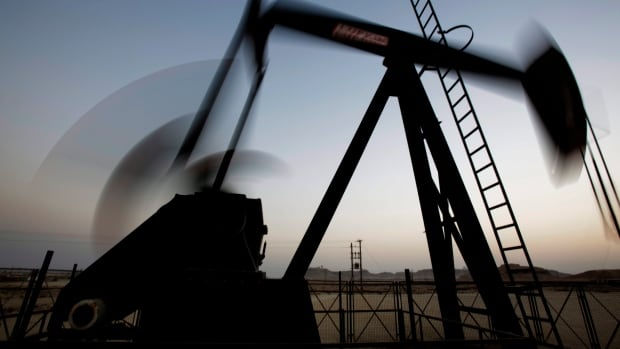 An oil pump works at sunset in the desert oil fields of Sakhir, Bahrain. OPEC can afford to wait out falling oil prices because of its low production costs.