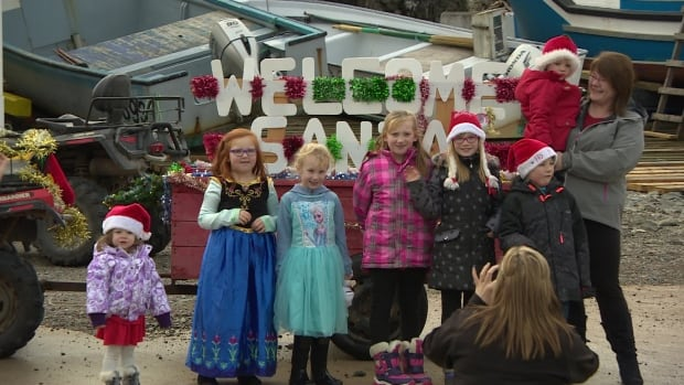 Children in South East Bight, an isolated community of less than 90 residents on Newfoundland's Burin Peninsula, gather in front of a 'Welcome Santa' sign on Dec. 15.