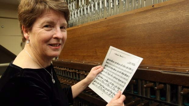 "Dr. Andrea McCrady, the Dominion carillonneur, holds the sheet music to ""Silent Night"" as she sits in the Peace Tower carillon on Parliament Hill, on Dec. 23, 2014. McCrady was among carillonneurs in 11 countries playing ""Silent Night"" on Dec. 24 to mark the 100th anniversary of the Christmas truce during the war."