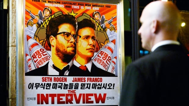 A security guard stands at the entrance of United Artists theatre during the premiere of the film The Interview. A limited release in independent theatres pulled in about $1 million US for the film on Christmas Day.