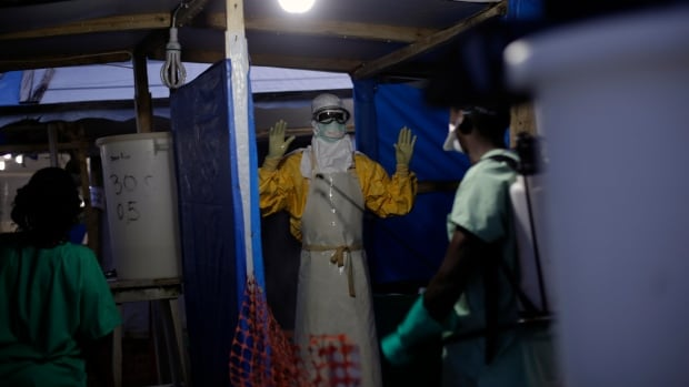 An Ebola health worker is sprayed as he leaves the contaminated zone at the Ebola treatment centre in  Gueckedou, Guinea.  The operation to fight Ebola in West Africa has hampered the campaigns against malaria, a preventable and treatable disease that is claiming many thousands of lives