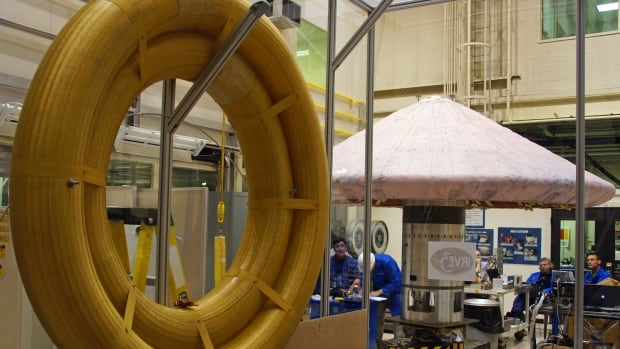 Technicians work on a Hypersonic Inflatable Aerodynamic Decelerator, background, made up of high-tech fabric rings similar to those seen in the foreground, at NASA Langley research centre in Hampton, Va.