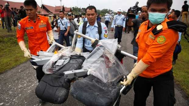 Parts of AirAsia QZ8501, recovered from the Java Sea, are carried by Indonesian airforce and search-and-rescue crew members after they were offloaded from a U.S. navy helicopter at the airport in Pangkalan Bun, Indonesia on Monday.