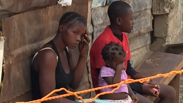 Members of the Bangura family are quarantined after a family member died of Ebola. Seventeen families are living under armed guard behind a rope cordoning them off from their community.