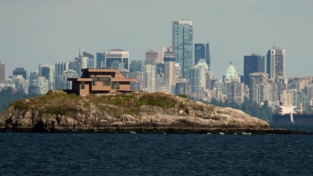 Downtown Vancouver is seen in the background as a house sits on top of a small island in West Vancouver, B.C. The average price of a detached house in Greater Vancouver is over $1 million, while the average sales price for any home was $638,500.