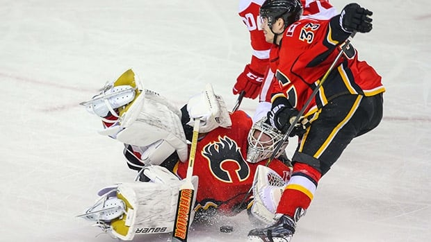Calgary Flames goalie Karri Ramo, bottom, and defenceman Raphael Diaz collide during the second period against the Detroit Red Wings Wednesday night. Ramo left the game with an apparent head injury.