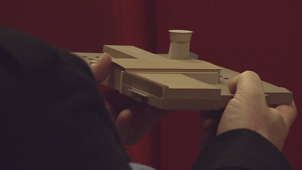 A resident holds a model of the new Gander International Airport, which will cost $40 million to build.