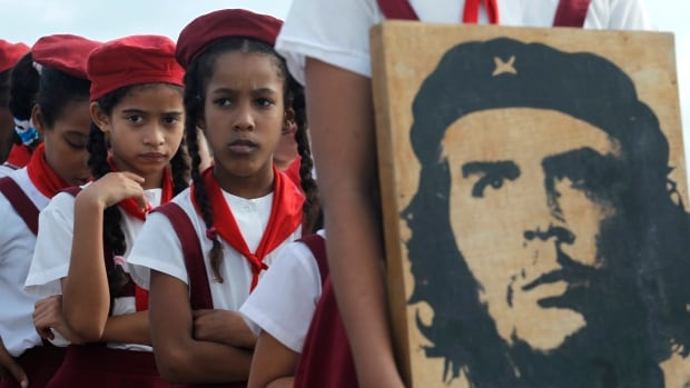 Students carry a photograph of Argentine revolutionary Ernesto (Che) Guevara, who helped Fidel Castro launch the Cuban Revolution in the 1950s and continues to have hero status in the country.