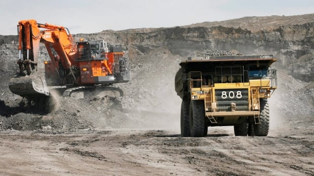A haul truck carrying a full load drives away from a mining shovel at the Shell Albian Sands oilsands mine near Fort McMurray, Alta., in 2008. Shell Canada says it will cut its workforce at the Muskeg River and Jackpine oilsands mines by less than 10 per cent.