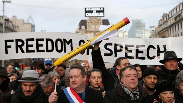 A man holds up a giant pencil during a march in Brussels on Jan. 11 for the victims of the Charlie Hebdo shootings in Paris.