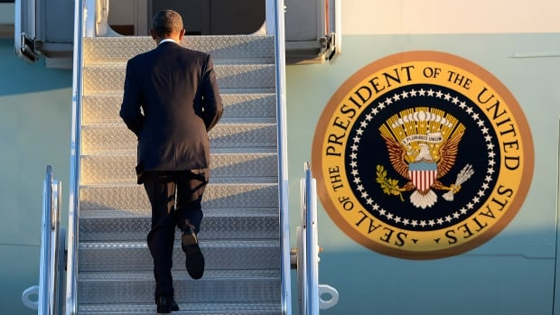 President Barack Obama boards Air Force One after a visit to Tennessee on Friday. He is being criticized by some American pundits for not flying to Paris for Sunday's massive unity rally.