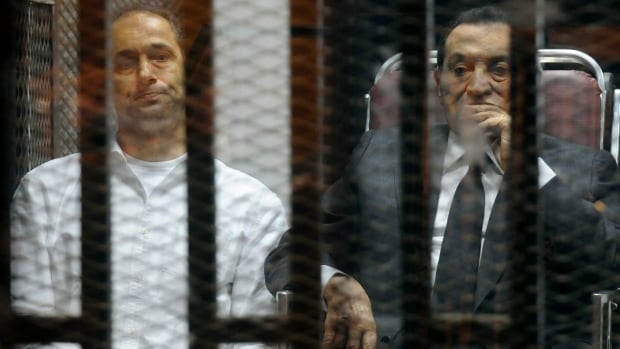 Egypt's ousted President Hosni Mubarak sits next to his son Gamal, left, inside a dock at the police academy court on the outskirts of Cairo on May 21, 2014.