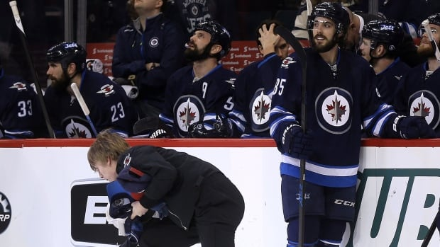 Winnipeg Jets' Mathieu Perreault looks on as rink staff pick up hats from the ice after he scored fours goals through two periods against the Florida Panthers on Tuesday.
