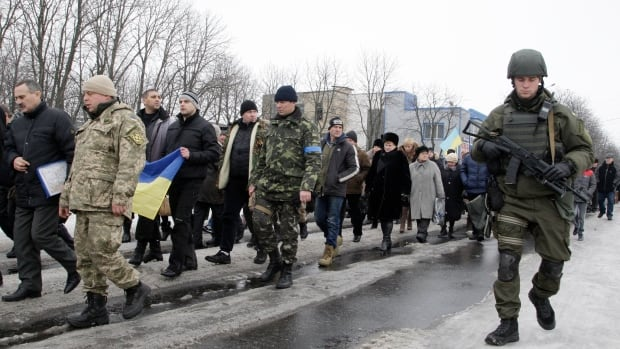People including members of the Ukrainian armed forces, attend a peace march in tribute to victims on board a passenger bus, which came under fire near the town of Volnovakha on Sunday.
