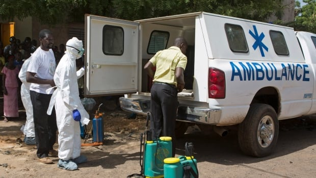 Health workers put on protective gear outside a mosque before disinfecting it, in Bamako in November 2014. Mali's health minister declared the country Ebola-free on Sunday.