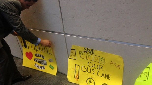Coun. Matthew Green of Ward 3 sets up pro-bus lane signs made by local children for a Jan. 21 council meeting. The city begins dismantling the lane on Monday.
